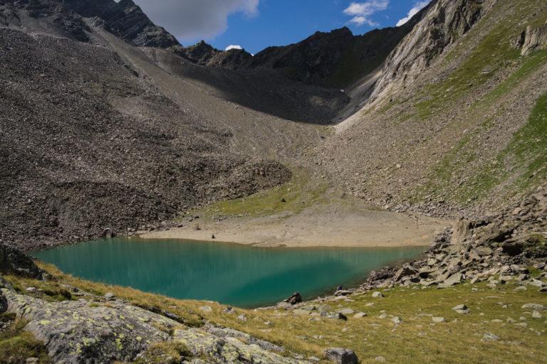 Das Bild zeigt den See blaugrün schimmernd in karger Berglandschaft.