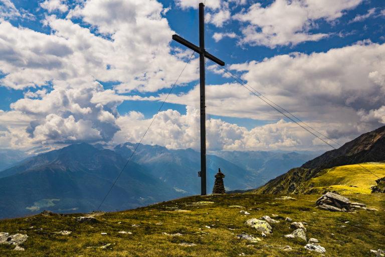 Das Gipfelkreuz am Niederjöchl im Vinschgau bei unterbrochener Wolkendecke.