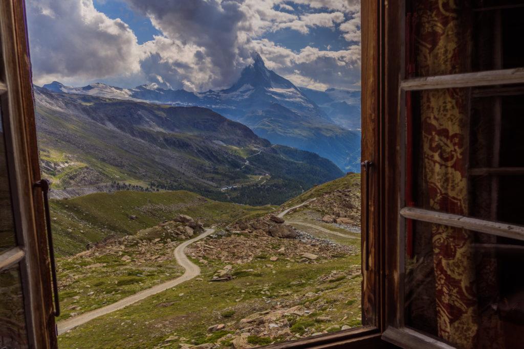 Das Foto zeigt den Blick aus einem geöffneten Fenster der Fluealphütte Richtung Matterhorn.