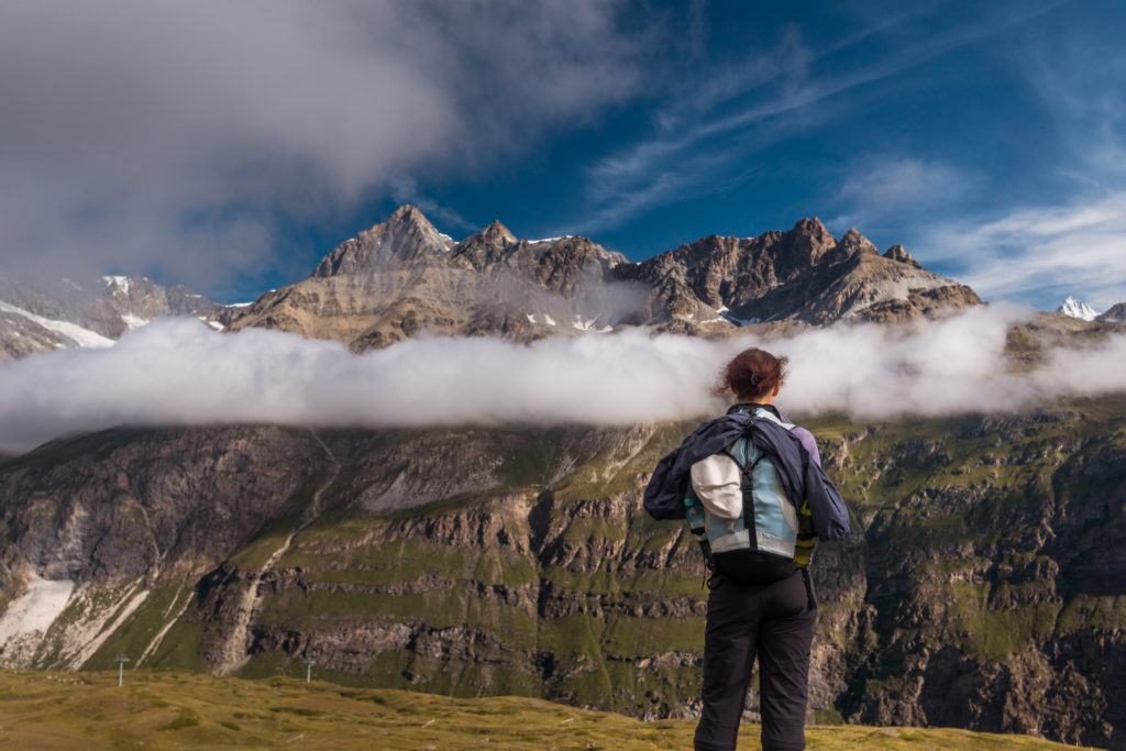 Das Bild zeigt eine Wanderin, die Richtung Berge blickt.